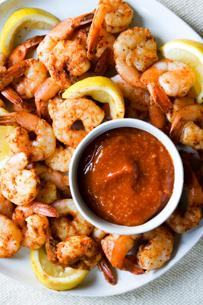 a bowl of cocktail sauce on a plate of squeezed lemons and steamed shrimp