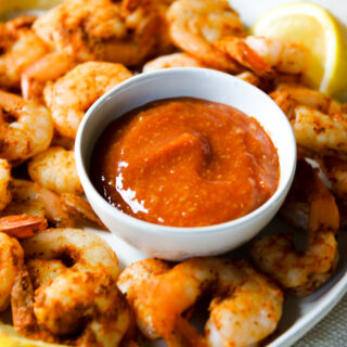 a bowl of cocktail sauce on a plate of steamed shrimp