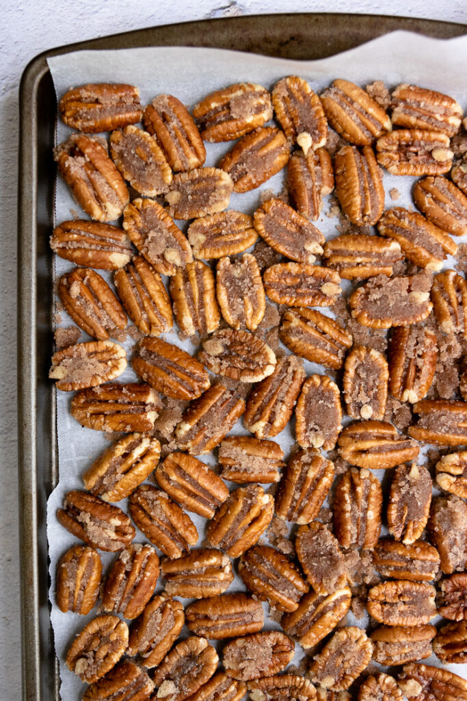 candied pecan halves on parchment paper on a cookie sheet