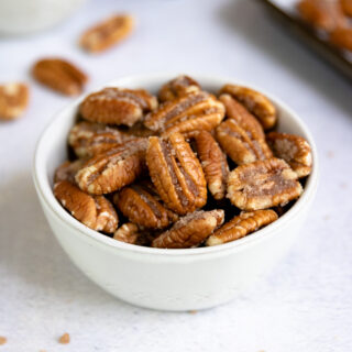 a small bowl of candied pecans with cinnamon and a cookie sheet in the background