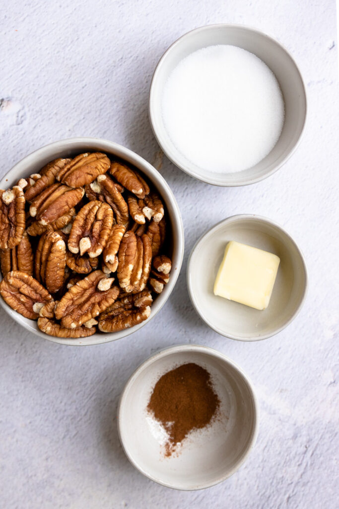 four white bowls with pecan halves, sugar, butter, and cinnamon