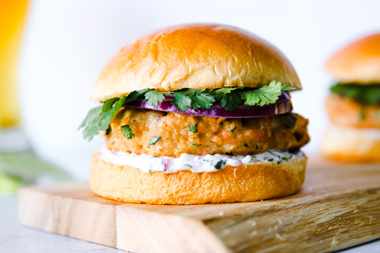a brioche bun, with cilantro, red onion slices, salmon patty, and mayonnaise