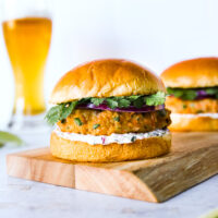 a grilled salmon burger on a wooden platter with a beer in the background
