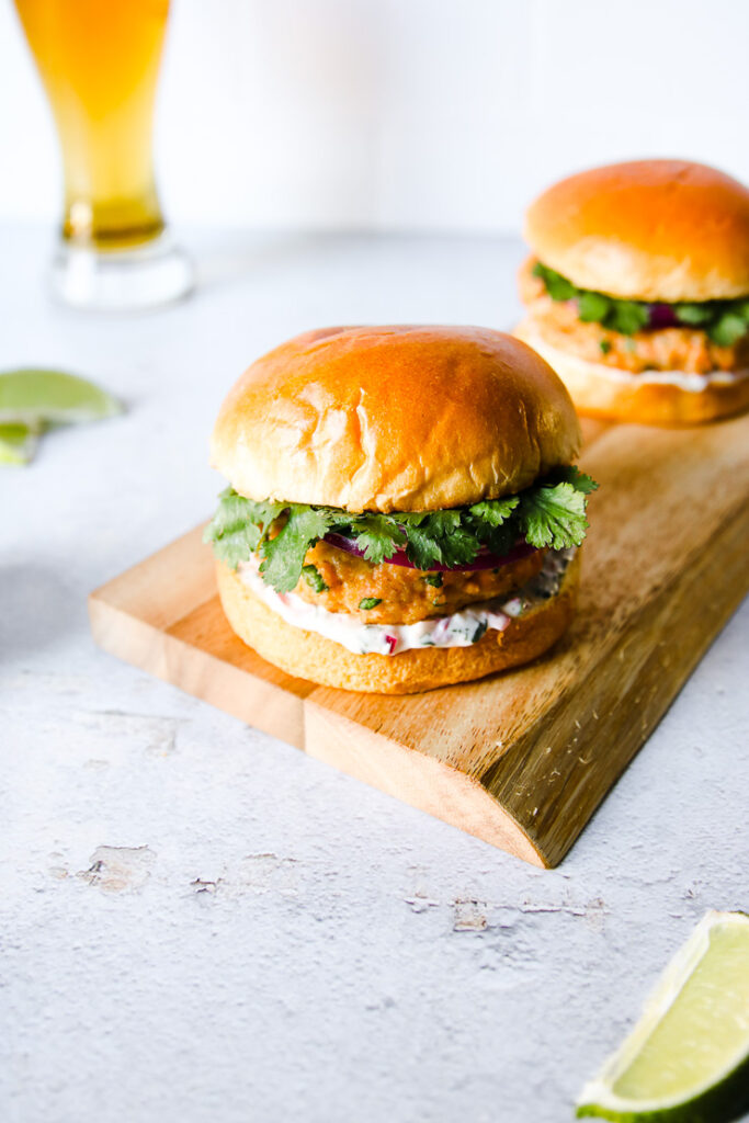 two grilled salmon burgers on a wood platter next to a beer