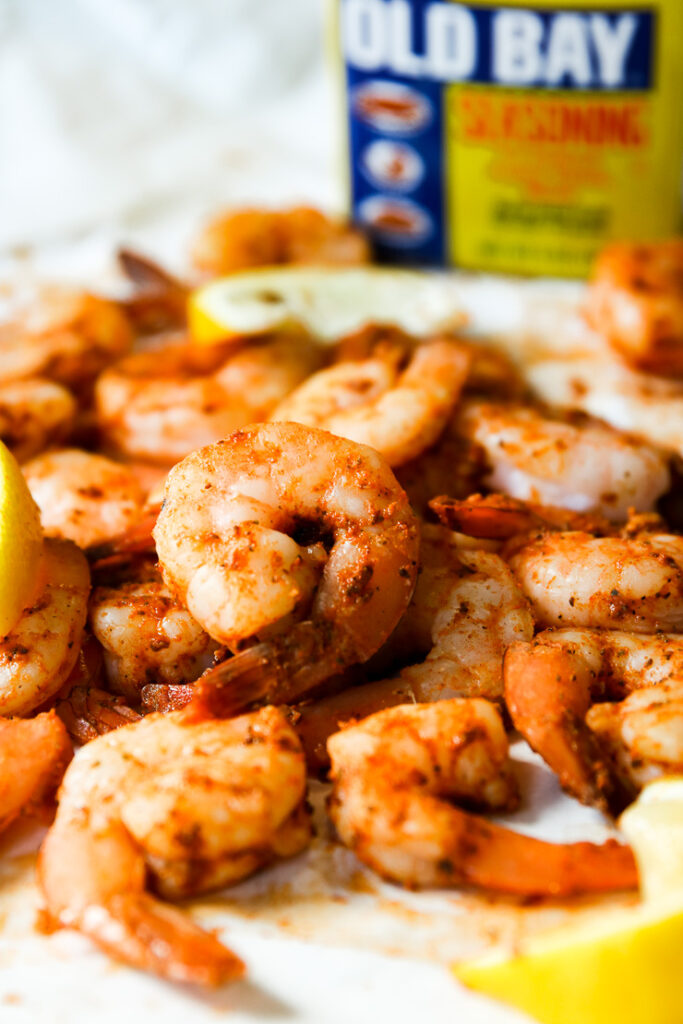 a pile of steamed shrimp, lemon slices, and container of old bay in the background