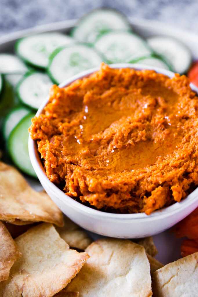 a close up of a bowl of roasted carrot hummus next to pita chips and sliced cucumbers