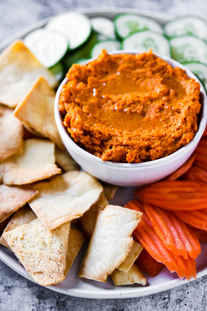 a plate of pita chips, carrot chips, and cucumber slices with a bowl of roasted carrot hummus