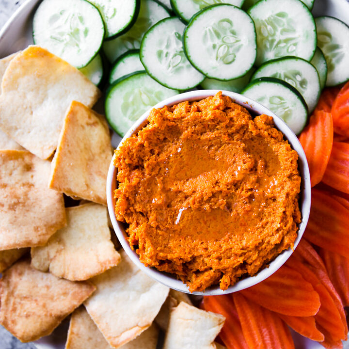 an overhead shot of roasted carrot hummus with veggies and pita chips on a plate